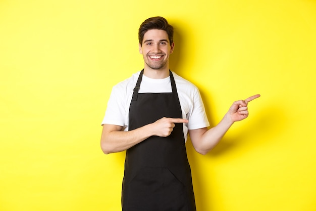 Garçom simpático apontando o dedo para a direita, mostrando seu logotipo ou oferta promocional, vestindo uniforme de avental preto, em pé sobre uma parede amarela