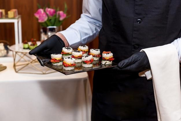 Garçom usando luvas pretas leva lanches em uma festa de feriado ou recepção de casamento