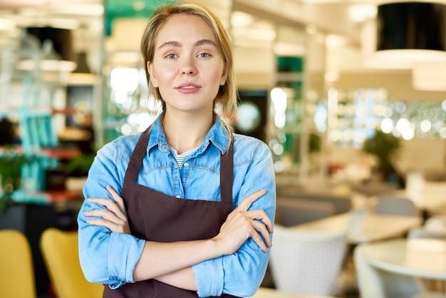 Garçonete adolescente confiante, trabalhando no café