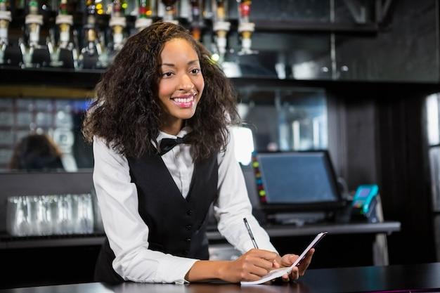 Garçonete, anotar um pedido no balcão de bar