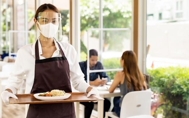 Garçonete asiática servindo comida novo normal.