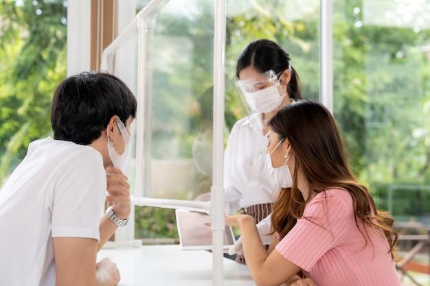 Garçonete asiática usa máscara e protetor facial usando um tablet para mostrar o menu eletrônico do restaurante