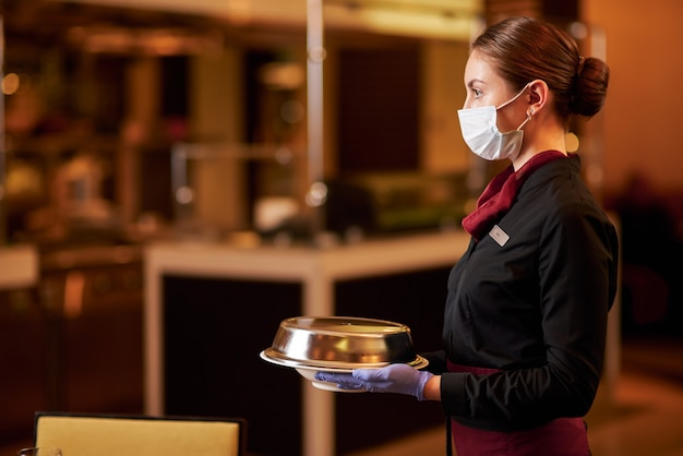 Garçonete atenta usando máscara enquanto serve comida