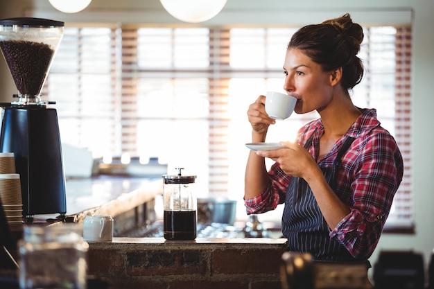Garçonete, bebendo um café