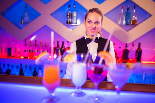 Garçonete bonita em pé no balcão de bar