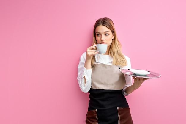 Garçonete caucasiana segurando uma xícara e uma bandeja isolada na parede rosa do estúdio