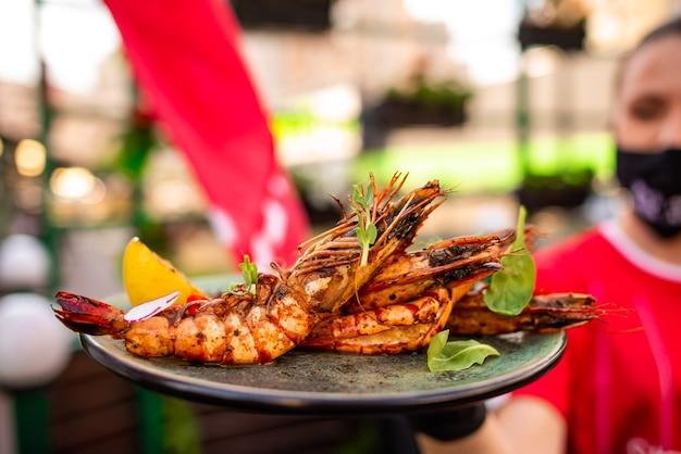 Garçonete com luvas pretas segurando um prato preto com deliciosos camarões lagostins