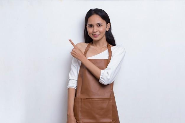 Garçonete de barista feliz jovem asiática apontando para diferentes direções com os dedos