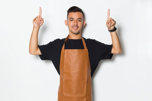 Garçonete de barista jovem feliz apontando para diferentes direções