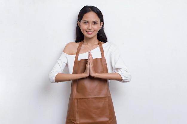 Garçonete de barista mulher asiática usando avental mostra gesto de boas-vindas isolado no fundo branco