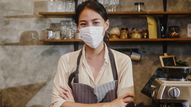 Garçonete de jovem asiática de retrato usa máscara médica, sentindo um sorriso feliz esperando por clientes após o bloqueio no café urbano.
