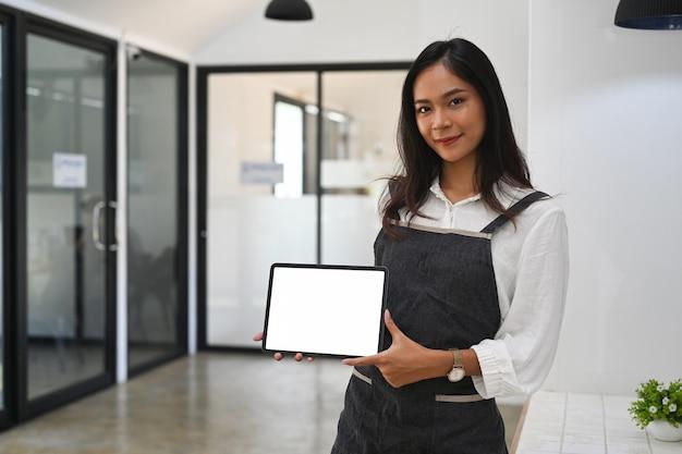 Garçonete de mulher asiática segurando e mostrando o tablet digital em pé na cafeteria.