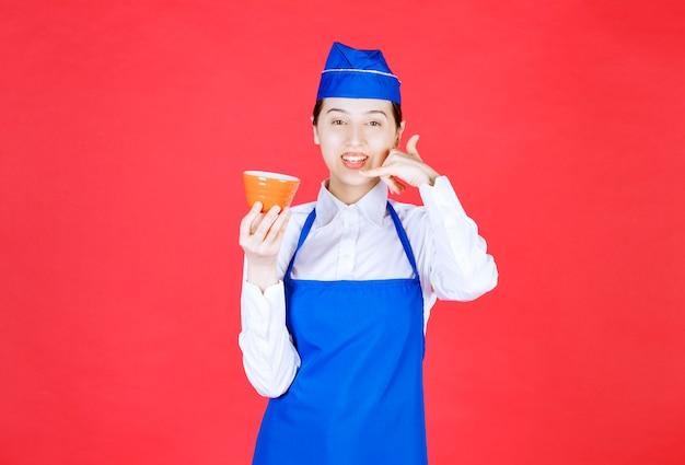 Garçonete de mulher de uniforme segurando uma tigela de laranja e fazendo gesto de telefonema.