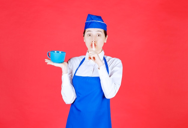 Garçonete de mulher de uniforme segurando uma xícara azul e fazendo sinal silencioso na parede vermelha.