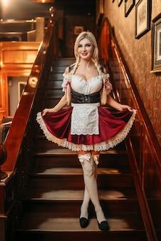 Garçonete de octoberfest com vestido de estilo tradicional na escada em pub vintage.