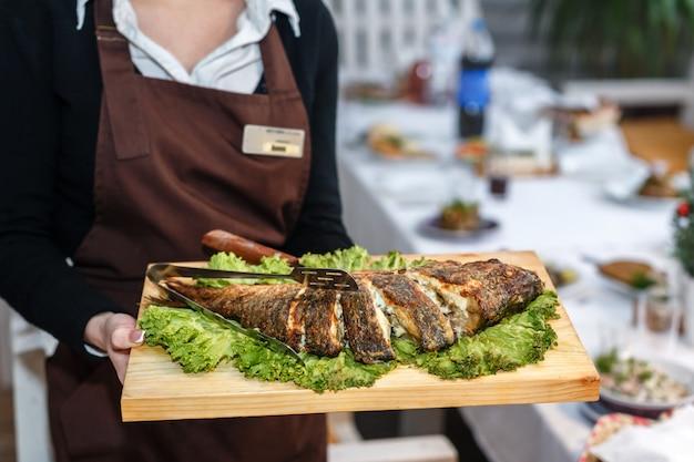 Garçonete de uniforme preto segurando uma placa de madeira com peixe assado em um restaurante