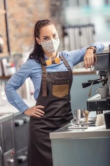 Garçonete elegante usa máscara protetora enquanto prepara um café expresso em uma cafeteria.