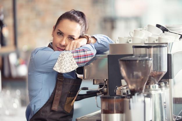 Garçonete entediada se encosta na máquina de café, sem trabalho a fazer, segurando uma máscara facial na mão.