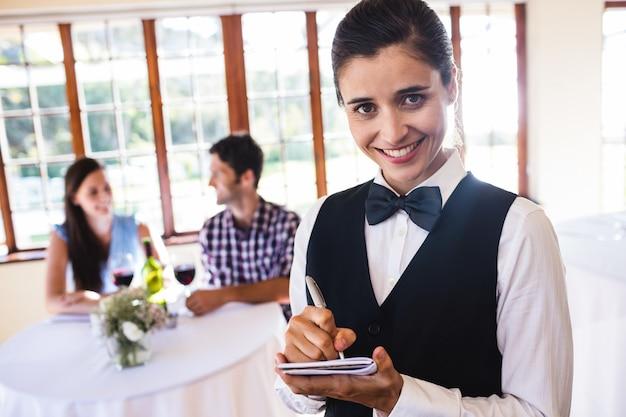 Garçonete, escrevendo a ordem no bloco de notas no restaurante