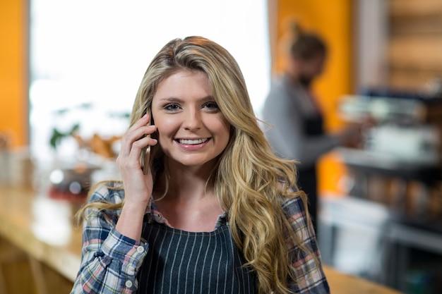 Garçonete, falando no celular em café