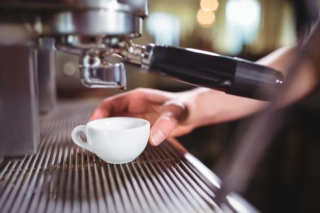 Garçonete fazendo chávena de café no contador na cozinha