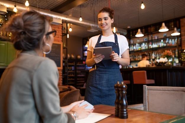Garçonete jovem e feliz com um tablet digital em pé ao lado de uma das mesas na frente de uma convidada e anotando seu pedido em um café ou restaurante