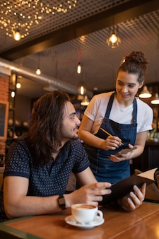 Garçonete jovem e feliz de avental, curvando-se sobre um dos clientes de um café ou restaurante enquanto escreve seu pedido no bloco de notas