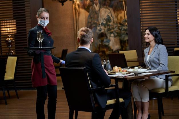 Garçonete mascarada aproximando-se de uma mesa para dois com um par de taças de vinho enquanto os convidados a observam com alegria