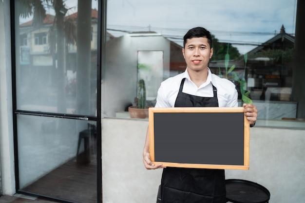 Garçonete masculina de café em pé segurando um quadro-negro