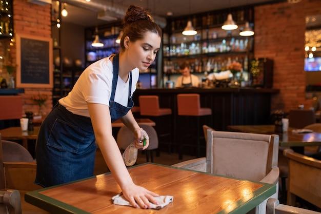 Garçonete muito jovem de avental curvada sobre a mesa de madeira enquanto usa detergente e espanador para limpá-la para os novos clientes do restaurante