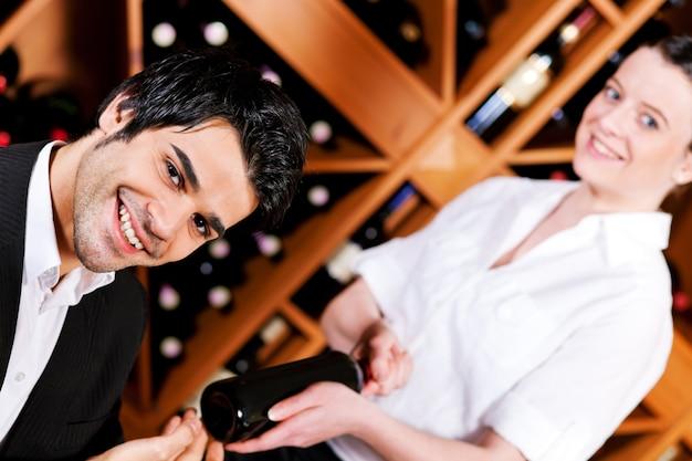 Garçonete no restaurante oferecendo vinho tinto