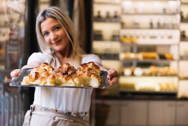 Garçonete oferecendo bandeja de croissant