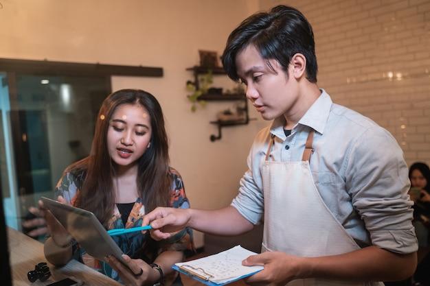 Garçonete oferecendo bebidas na lista de menu para uma cliente garota em um café