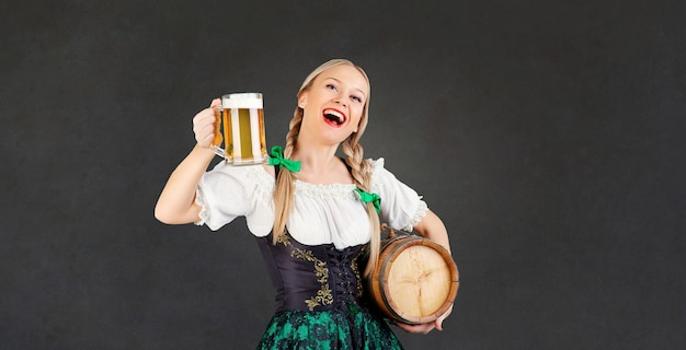 Garçonete oktoberfest em traje nacional com uma caneca de cerveja