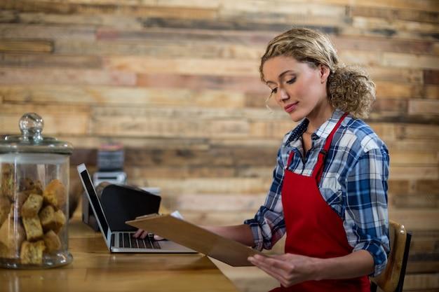 Garçonete, olhando para a área de transferência enquanto estiver usando o laptop no café