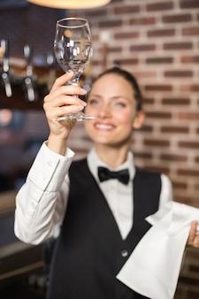 Garçonete, olhando para um copo de vinho