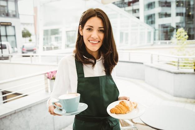 Garçonete, posando com café e croissant no café