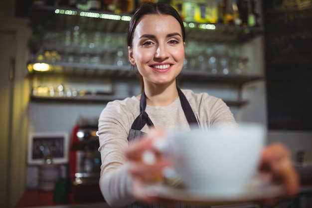 Garçonete que serve uma xícara de café para o cliente