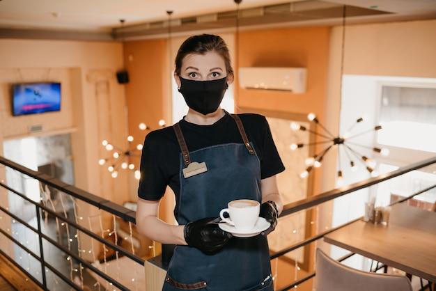 Garçonete que usa uma máscara preta e luvas descartáveis