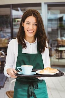 Garçonete, segurando a bandeja com café e croissant no café