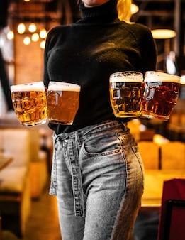 Garçonete, segurando canecas de cerveja embaçada