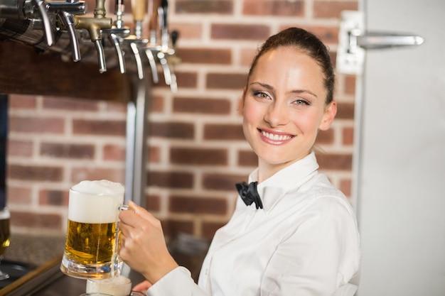 Garçonete segurando cervejas enquanto sorrindo para a câmera