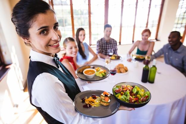 Garçonete, segurando comida no prato no restaurante