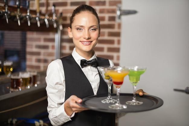 Garçonete, segurando o prato com cocktails