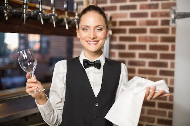 Garçonete, segurando um copo de vinho e toalha