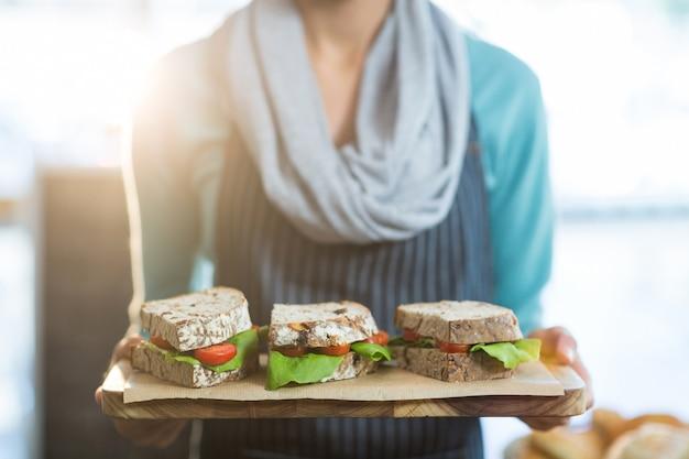 Garçonete, segurando uma bandeja com sanduíches no café