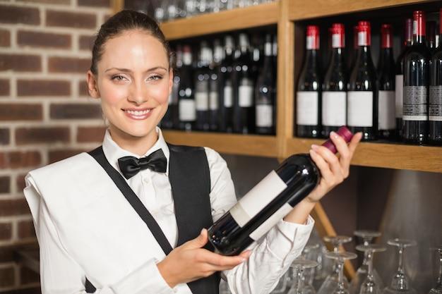 Garçonete, segurando uma garrafa de vinho