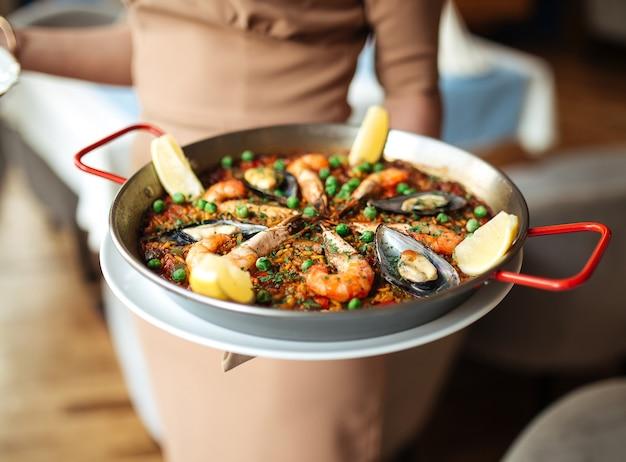 Garçonete segurando uma paella de arroz com frutos do mar