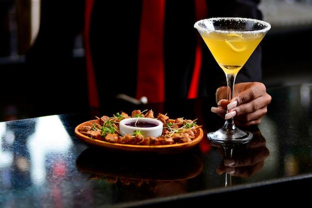 Garçonete servindo aperitivo de laranja e salgadinhos de carne em um bar escuro