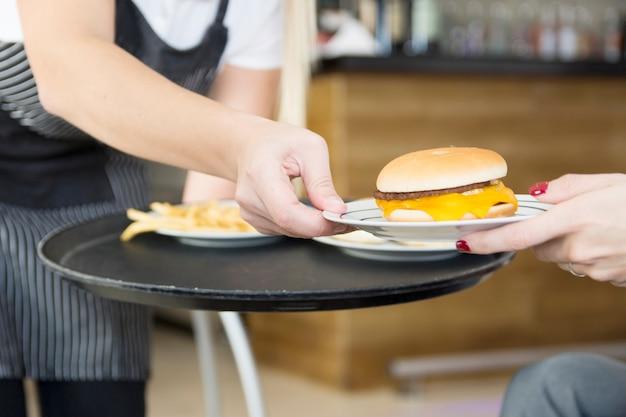 Garçonete, servindo, hambúrguer, para, femininas, cliente, em, a, restaurante